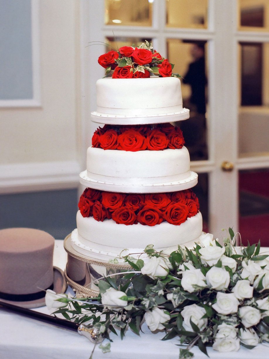 A three tier Fruit cake with Royal Icing dressed with Red Roses.